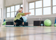 Senior woman doing exercise with her personal trainer. Senior women doing exercise with her personal trainer at gym. Gym instructor assisting elder women in her Royalty Free Stock Image