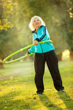 Senior Woman doing Exercises in Nature. 70 years old Senior Woman doing Exercises with the Plastic Hoop at the Green Meadow in the Bright Autumn Evening Stock Photos