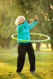 Senior Woman doing Exercises in Nature. 70 years old Senior Woman doing Exercises with the Plastic Hoop at the Green Meadow in the Bright Autumn Evening Stock Image