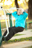 Senior Woman doing Exercises Outdoors. 70 years old Senior Woman doing Exercises for Legs Outdoors in the Bright Autumn Evening Stock Image