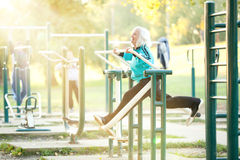 Senior Woman doing Exercises Outdoors. 70 years old Senior Woman doing Exercises for Legs Outdoors in the Bright Autumn Evening Stock Photography