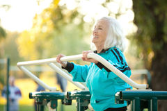 Senior Woman doing Exercises Outdoors. 70 years old Senior Woman doing Exercises for Legs Outdoors in the Bright Autumn Evening Royalty Free Stock Images