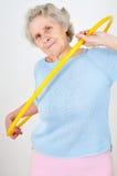 Senior woman doing gymnastic with hula-hoop Stock Images