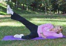Senior woman doing leg left exercise royalty free stock photography