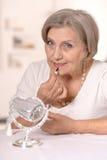 Senior woman doing makeup Stock Photo