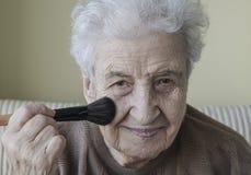 Senior woman doing makeup Stock Photography
