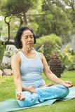 Senior woman doing meditation for yoga. At garden in the morning stock photography