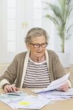 Senior woman doing paperwork Stock Images