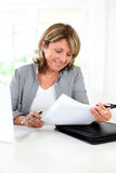 Senior woman doing paperwork with help of internet Royalty Free Stock Photography