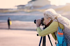 Senior woman doing photography on a beach in Florida Royalty Free Stock Image