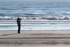 Senior woman doing photography on a beach in Florida. Senior woman taking a photo of the landscape on a beach in Florida with waves rolling in the background on Royalty Free Stock Photos