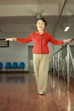 A senior woman doing physical exercise. An eld woman is doing physical exercise by the handrail with her hands stretching out in the sport room royalty free stock photo