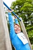 Senior woman is doing a chin-up. Senior woman doing a pull-up on the trim you course in nature stock photo