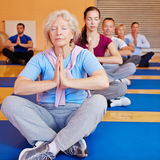Senior woman doing relaxation. Senior women doing relaxation exercise in yoga class in a gym Royalty Free Stock Image