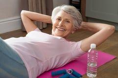 Senior woman doing crunches stock photo