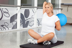 Senior woman doing stretching. Exercises on gym mat in fitness center Royalty Free Stock Photos