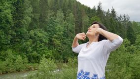 Senior woman doing a stretching exercise for the upper arms outside over landscape of forest and mountains. HD stock video footage