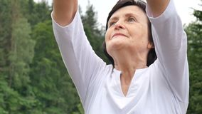 Senior woman doing a stretching exercise for the upper arms outside over landscape of forest and mountains. HD stock video