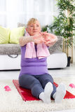 Senior woman doing stretching on a mat Stock Photography