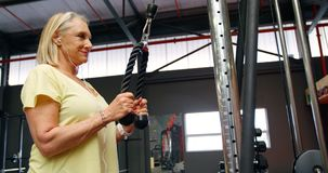 Senior woman doing triceps exercise in fitness studio 4k