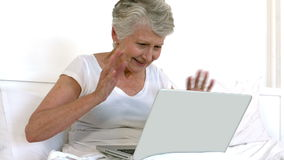 Senior woman doing a video chat. On bed stock video