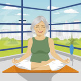 Senior woman doing yoga exercises in lotus position sitting on mat Stock Image