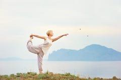 Senior woman doing yoga exercises Stock Image