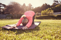 Senior woman doing yoga outdoors in gentle morning sunlight Stock Photo