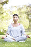 Senior Woman Doing Yoga In Park Royalty Free Stock Image