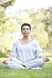 Senior Woman Doing Yoga In Park Royalty Free Stock Photos