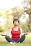 Senior Woman Doing Yoga In Park Stock Photo