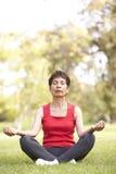 Senior Woman Doing Yoga In Park Stock Photo