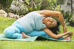 Senior woman doing yoga at park Stock Images