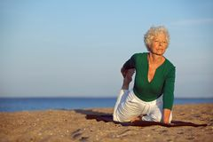 Senior woman doing yoga by the sea Royalty Free Stock Images
