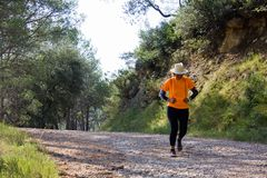 Senior woman dressed in sports clothes and a hat running down the mountain stock images
