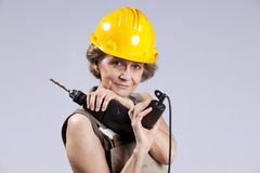 Senior woman with a drill tool Stock Photos