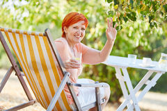 Senior woman with a drink on a deck chair Stock Photo