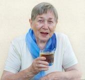 Senior woman drinking Stock Images