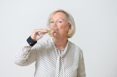 Senior woman drinking champagne Royalty Free Stock Images