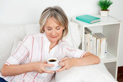 Senior woman drinking coffee Stock Images