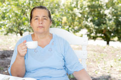 Senior woman drinking coffee in the garden Stock Photo