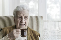 Senior woman drinking coffee Stock Photo