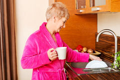 Senior woman drinking coffee in kitchen and washing plate Royalty Free Stock Photos
