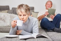 Senior woman drinking cup of coffee. Senior women drinking cup of coffee and reading book at home Royalty Free Stock Images