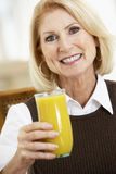 Senior Woman Drinking A Glass Of Orange Juice Stock Images