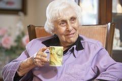 Senior woman drinking hot beverage royalty free stock photography
