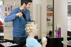A senior woman drinking a hot beverage whilst having her hair dried by a male hairdresser stock images