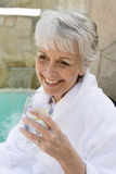 Senior Woman Drinking Lime Water Outdoors. Closeup of a smiling senior woman drinking lime water outdoors Stock Images