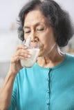 Senior woman drinking milk. Senior Asian woman drinking milk at home Stock Image