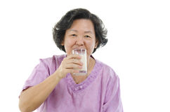 Senior woman drinking milk. Portrait of Asian senior adult woman drinking a glass soy milk, isolated on white background Stock Image